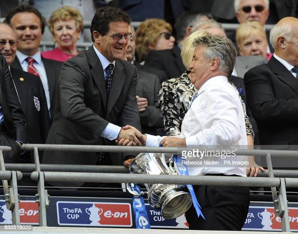 England manager Fabio Capello shakes hands with Chelsea manager Guus Hiddink as he collects the FA Cup Trophy
