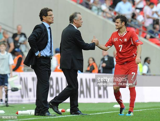 England manager Fabio Capello stands on the touchline as Switzerland manager Ottmar Hitzfeld shakes hands with Tranquillo Barnetta