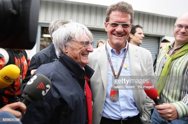 England manager Fabio Capello with President and CEO of Formula One Bernie Ecclestone are swamped by the media in the paddock during the practice...
