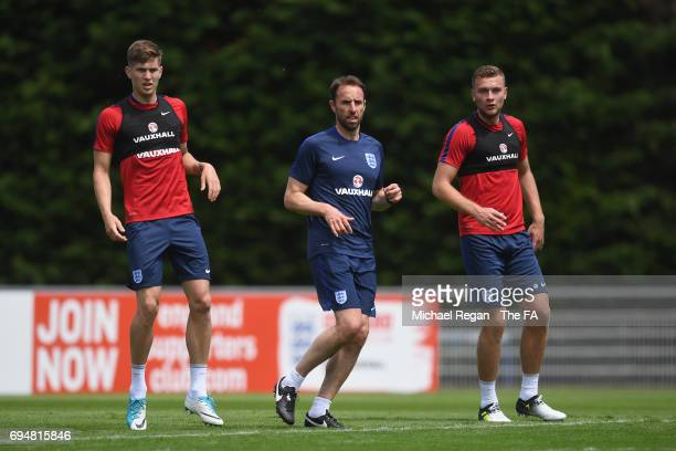 England manager Gareth Southgate looks on with John Stones and Ben Gibson during the England training session at Stade Omnisports on June 11 2017 in...