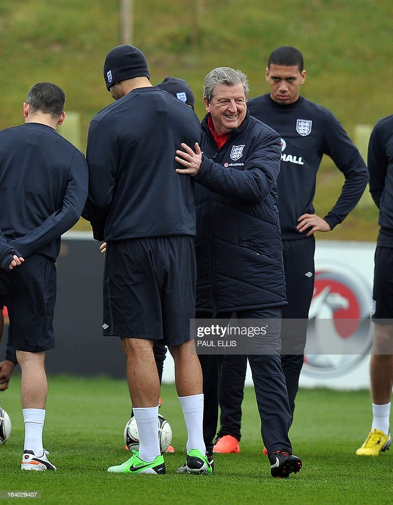 England manager Roy Hodgson shakes hands with Joleon Lescott during a training session at the St George's Park training complex, near Burton-upon-Trent, central England on March 19, 2013 ahead of their 2014 World Cup qualifier football match against San Marino on March 22.
