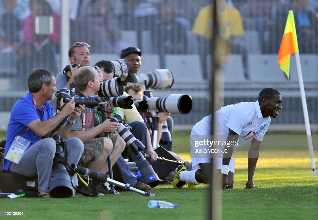 England national football team Shaun Wright-Phillips (R) falls down in front of photographers during a public training match against South African local team Platinum Stars FC at Moruleng stadium near Rustenburg on June 7, 2010 ahead of the start of the 2010 World Cup football tournament on June 11.