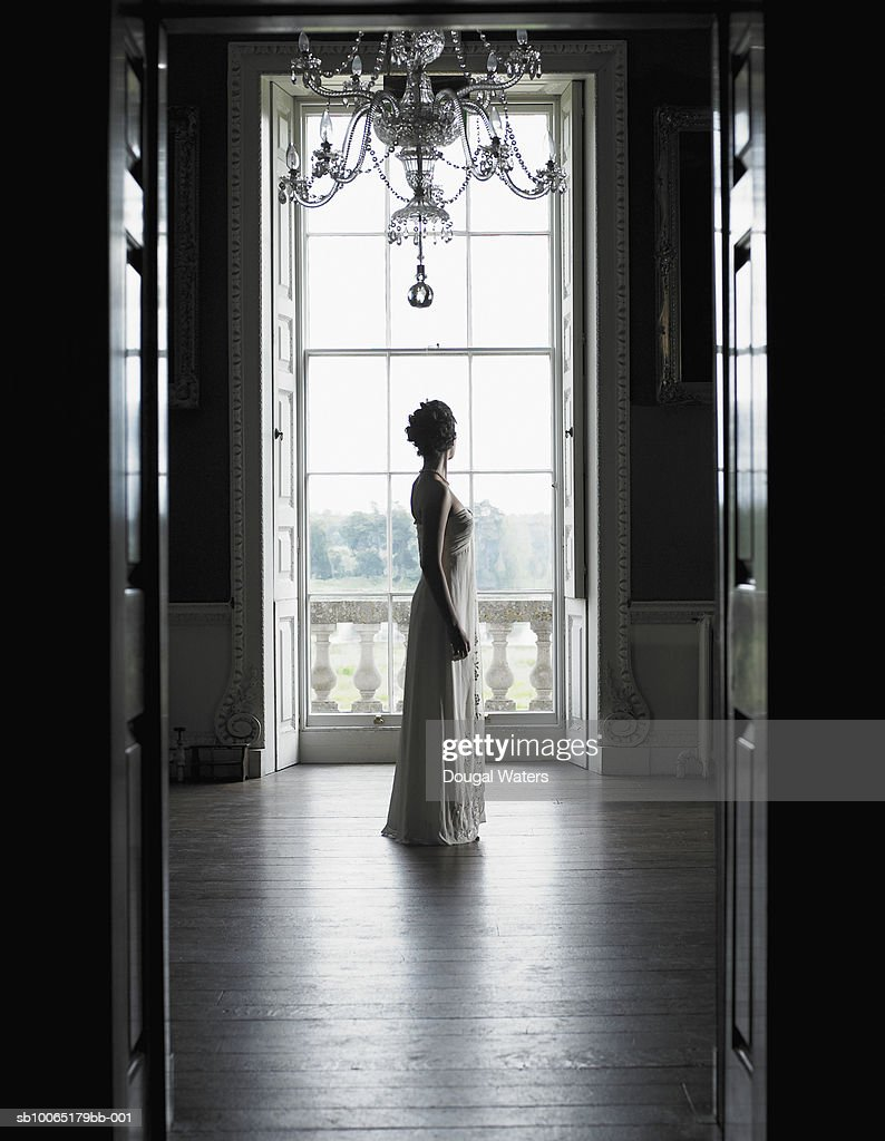 England, Norfolk, Wolterton Hall, Young woman wearing evening freestanding in hall, side view