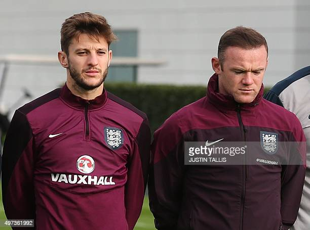 England player Adam Lallana and captain Wayne Rooney observe a minute of silence in tribute to victims of the November 13 Paris attacks during a team...