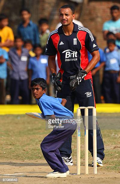England player Ajmal Shahzad keeps wicket as a boy prepares to play a shot during a game of cricket during a visit by England players to promote the...