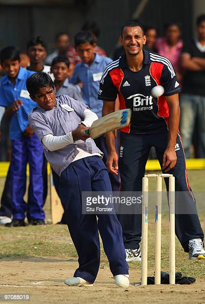 England player Ajmal Shahzad keeps wicket with a smile as a boy plays a shot during a game of cricket during a visit by England players to promote...