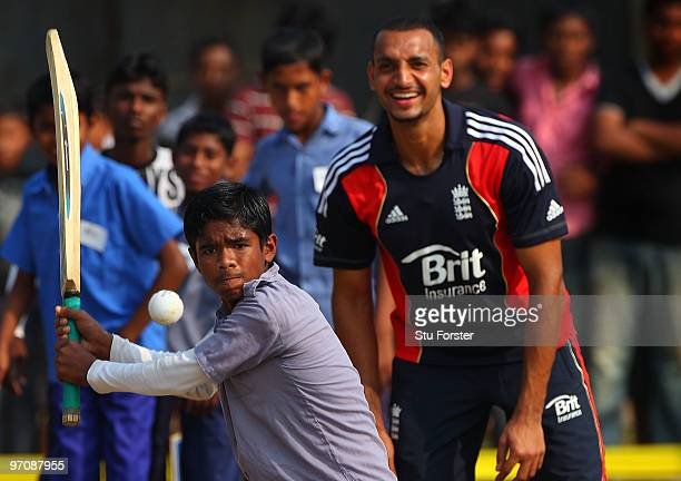 England player Ajmal Shahzad keeps wicket with a smile as a boy prepares to play a shot during a game of cricket during a visit by England players to...