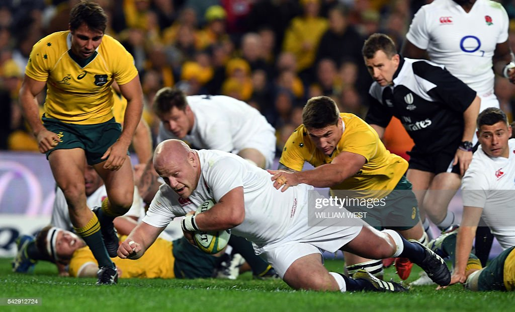 England player Dan Cole (C) crashes over to score against Australia during the third rugby union Test match in Sydney on June 25, 2016. / AFP / WILLIAM