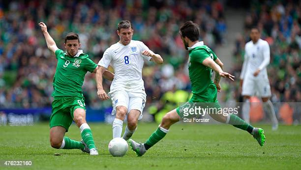 England player James Milner is challenged by Shane Long and Harry Arter during the International friendly match between Ireland and England at Aviva...