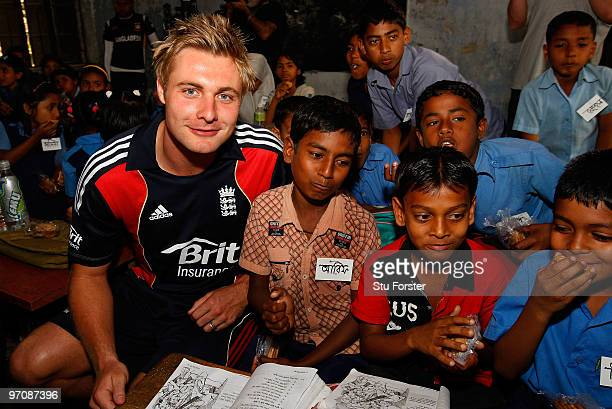 England player Luke Wright sits by school children eating their buiscuits during a visit by England players to promote the World Feeding Programme in...