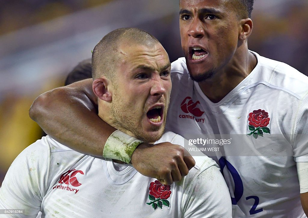 England player Mike Brown (L) is congratulated by teammate Anthony Watson (R) after scoring against Australia during the third rugby union Test match in Sydney on June 25, 2016. / AFP / WILLIAM