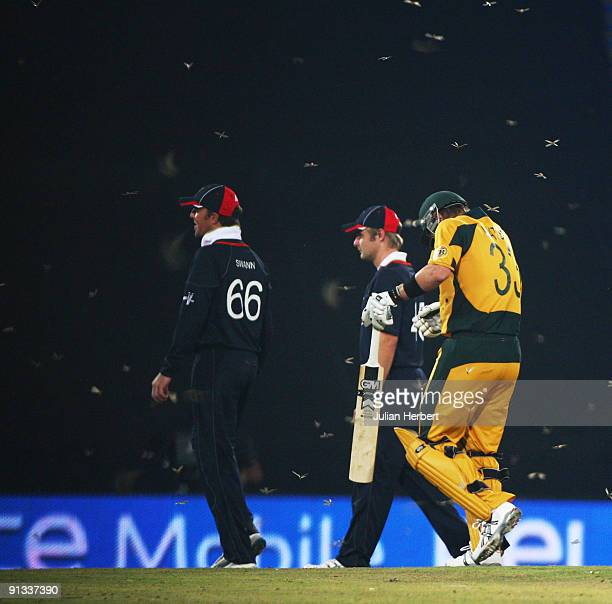 England players Graeme Swann and Luke Wright leave the field with Australian batsman Shane Watson before Australias innings when a swarm of flying...