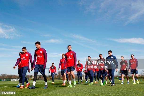 England players including midfielder Jake Livermore midfielder Dele Alli and defender Kyle Walker walk to a another pitch for a training session at...