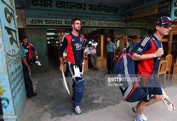 England players Kevin Pietersen and Joe Denly make their way to the batting nets past a local furniture shop during England nets practice at Shere...