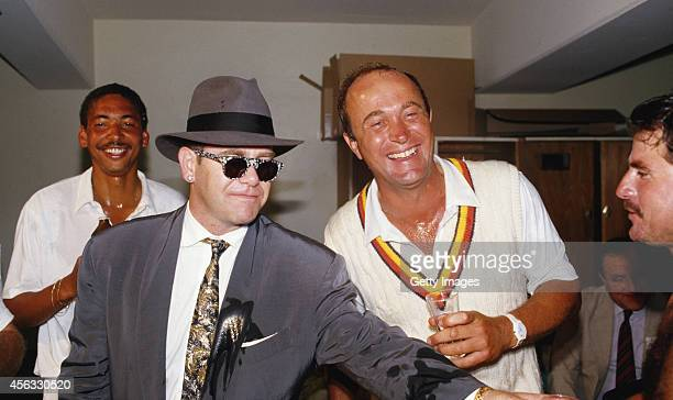 England players Phillip de Freitas Phil Edmonds and Allan Lamb share a joke and their champagne with singer Elton John in the dressing room after...
