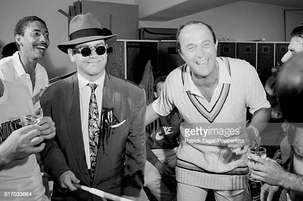 England players Phillip DeFreitas and Phil Edmonds share a joke and their champagne with singer Elton John in the dressing room after England had...