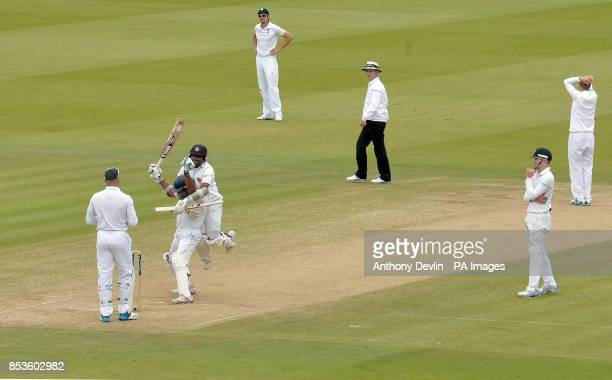 England players react as Sri Lanka's Kumar Sangakkara is congratulated by Mahela Jayawardene scoring his first century at Lord's during day three of...