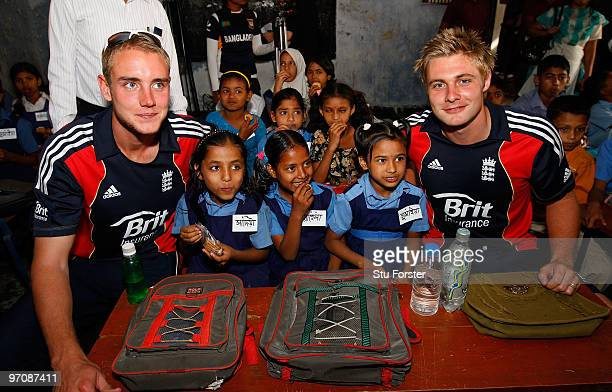 England players Stuart Broad and Luke Wright sit by school children eating their buiscuits during a visit by England players to promote the World...