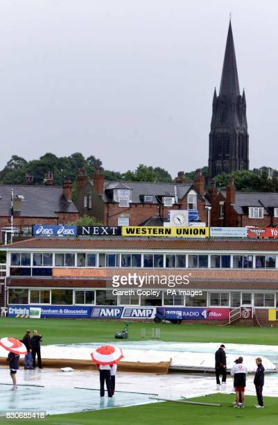 England players take shelter under their umbrellas as they inspect the pitch at Headingley Leeds as rain delays the start of play in the Fourth...