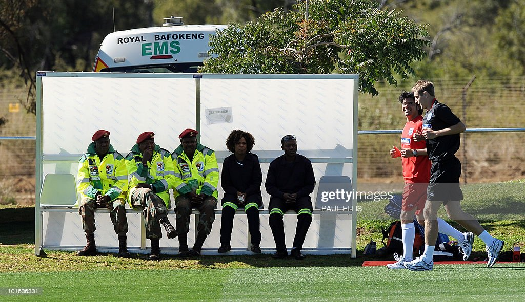 England replacement defender Michael Dawson (R) runs past medical staff during a training session at the Royal Bafokeng Sports Campus near Rustenburg on June 5, 2010. Dawson was flown from England to replace captain Rio Ferdinand after he injured his knee during the team's first training session in the country on June 4.