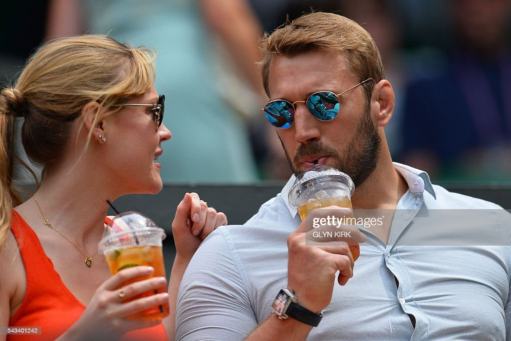 England rugby player Chris Robshaw (R) sits with singer Camilla Kerslake (L) in the royal box as they prepare to watch US player Serena Williams play Switzerland's Amra Sadikovic on Centre Court during their women's singles first round match on the second day of the 2016 Wimbledon Championships at The All England Lawn Tennis Club in Wimbledon, southwest London, on June 28, 2016. / AFP / GLYN