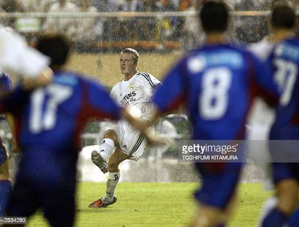 England soccer star David Beckham watches a ball in a free kick to score the first goal during a friendly match between Spanish team Real Madrid and...