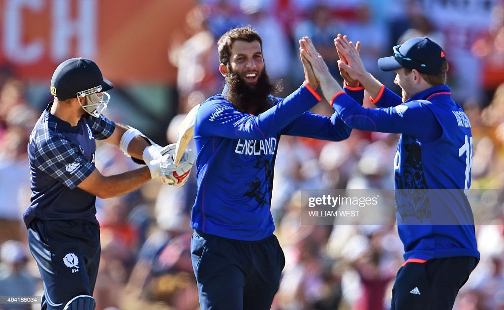 England spinner Moeen Ali is congratulated by his captain Eoin Morgan after dismissing Scotland batsman Kyle Coetzer during their 2015 Cricket World...