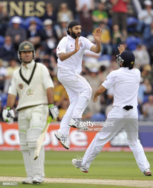 England spinner Monty Panesar celebrates with teammate Alastair Cook after dismissing Australian batsman Ricky Ponting on the third day of the first...