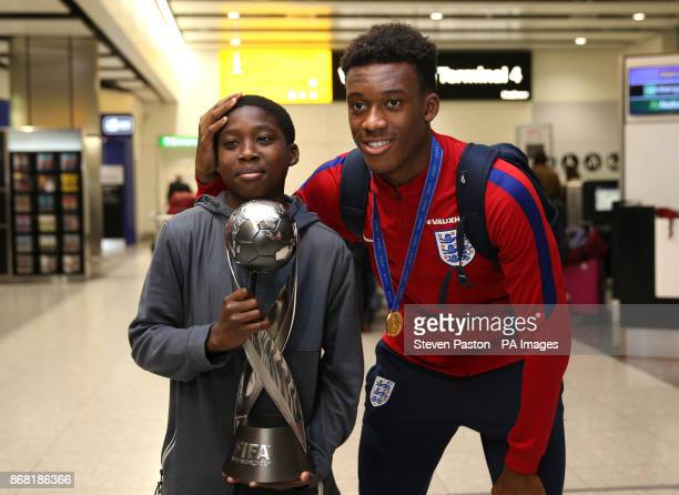 England U'17s Callum HudsonOdoi poses with his brother and the World Cup as the Under17 World Cup winning side arrive back to the UK at Heathrow...