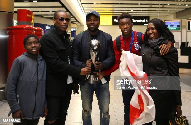 England U'17s Callum HudsonOdoi poses with his family and the World Cup as the Under17 World Cup winning side arrive back to the UK at Heathrow...