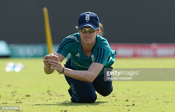England women cricketer Lydia Greenway dives for a catch at a practice session at the Feroz Shah Kotla stadium in New Delhi on March 29 2016 on the...