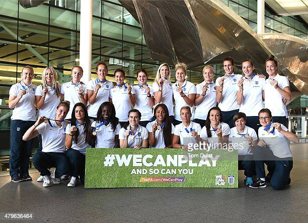 England Women's team pose for photos during their arrival from the World Cup at Heathrow Airport on July 6 2015 in London England