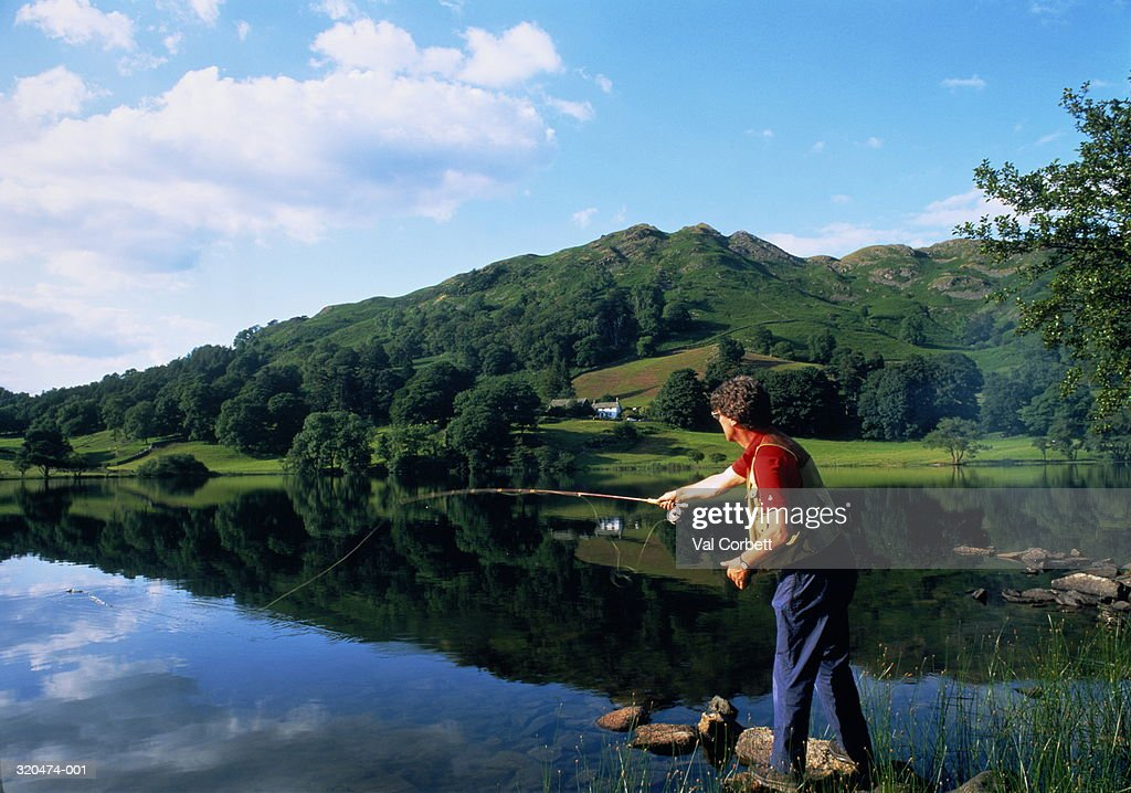 England,Cumbria,Lake District, Loughrigg Tarn,man fishing in lake : Stock Photo