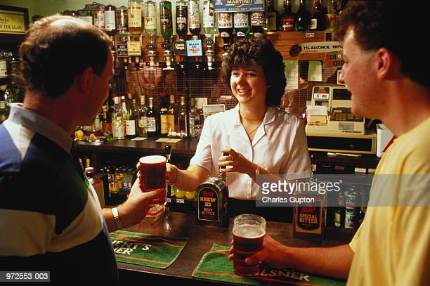 England,London,barmaid serving customers in typical public house
