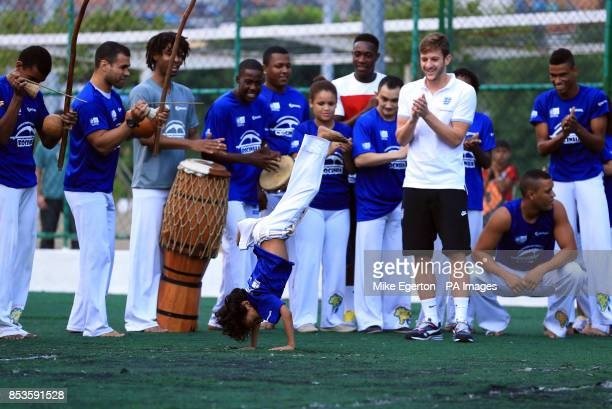 England's Adam Lallana applauds as he watches a Capoeira dance demonstration during a visit to the Complexo Esportivo da Rocinha Rio de Janeiro Brazil