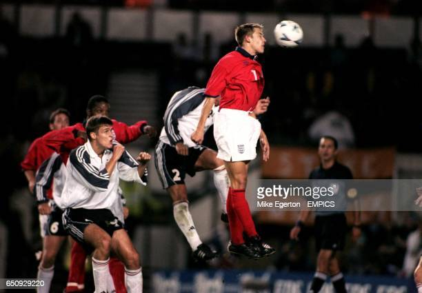 England's Alan Smith jumps with Germany's Manuel Benthien