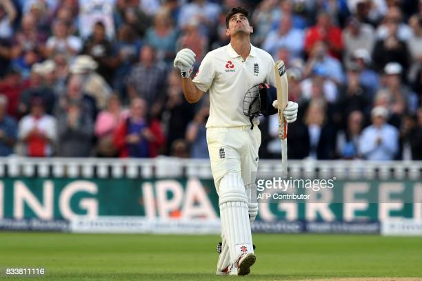 England's Alastair Cook celebrates after reaching his century during play on the opening day of the first Test cricket match between England and the...