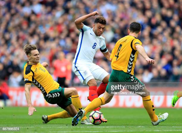England's Alex OxladeChamberlain battles for the ball with Lithuania's Arturas Zulpa and Lithuania's Tadas Kijanskas during the World Cup Qualifying...