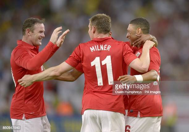 England's Alex OxladeChamberlain celebrates scoring their first goal of the game with teammate James Milner and Wayne Rooney