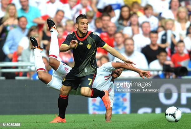 England's Alex OxladeChamberlain goes to ground after a challenge from Belgium's Dries Mertens