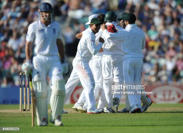 England's Andrew Strauss walks off after being caught by South Africa's Vernon Philander off the bowling of Imran Tahir during the Investec first...