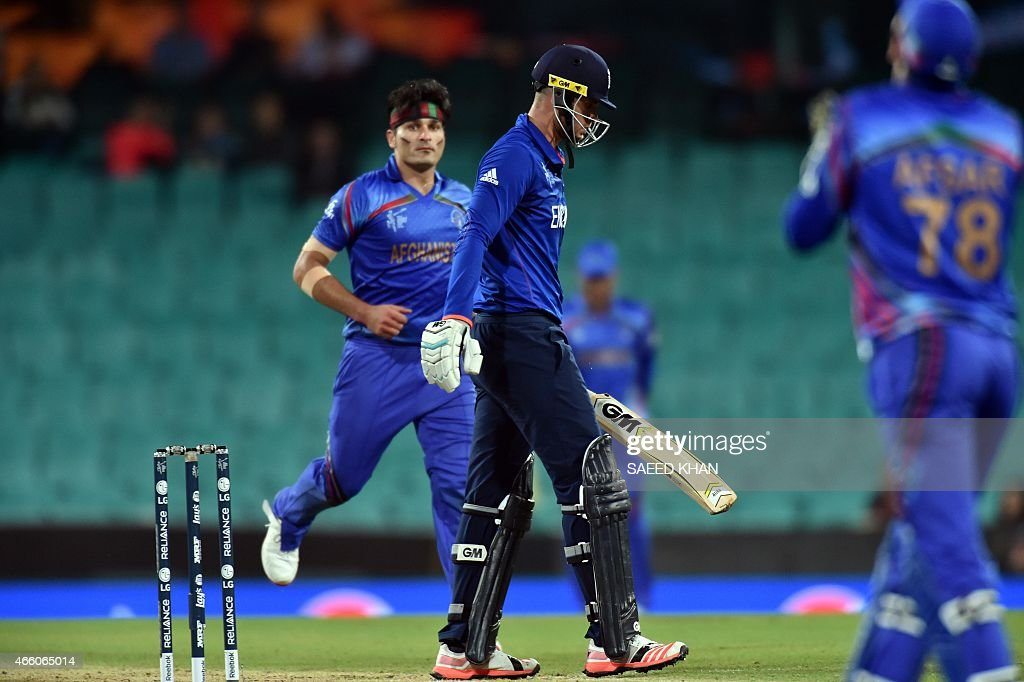 England's batsman Alex Hales (C) walks off the field following his dismissal off Afghanistan paceman Hamid Hassan (L) during the 2015 Cricket World Cup Pool A match between England and Afghanistan at the Sydney Cricket Ground on March 13, 2015. AFP PHOTO/ Saeed KHAN