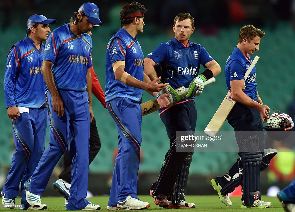 England's batsman Ian Bell (2nd R) talks to Afghanistan player Hamid Hassan (C) as they walk off the field with fellow batsman James Taylor during the 2015 Cricket World Cup Pool A match between England and Afghanistan at the Sydney Cricket Ground on March 13, 2015. AFP PHOTO/ Saeed KHAN