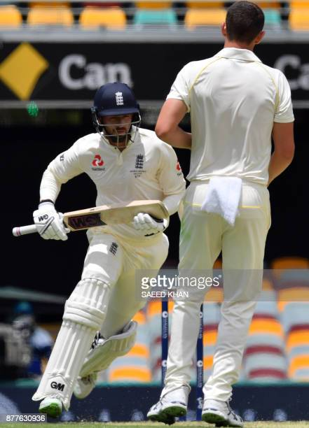 England's batsman James Vince runs between the wickets as Australia's Josh Hazlewood look on during the first day of the first cricket Test of Ashes...
