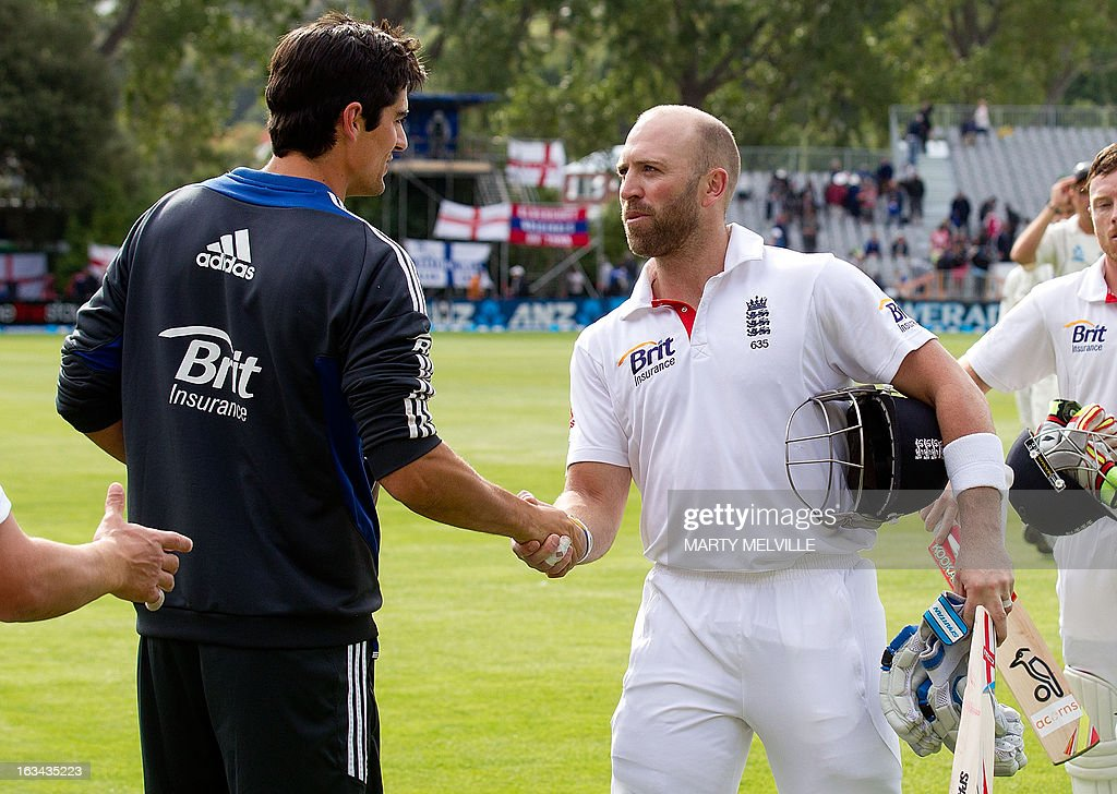 England's batsman Matt Prior (R) shakes hands with team captain Alastair Cook at the end of play during day four of the first international cricket Test match between New Zealand and England played at the University Oval park in Dunedin on March 10, 2013. AFP PHOTO / Marty MELVILLE