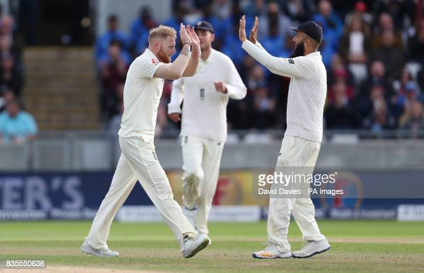 England's Ben Stokes celebrates taking the wicket of West Indies Shai Hope with Moeen Ali during day three of the First Investec Test match at...