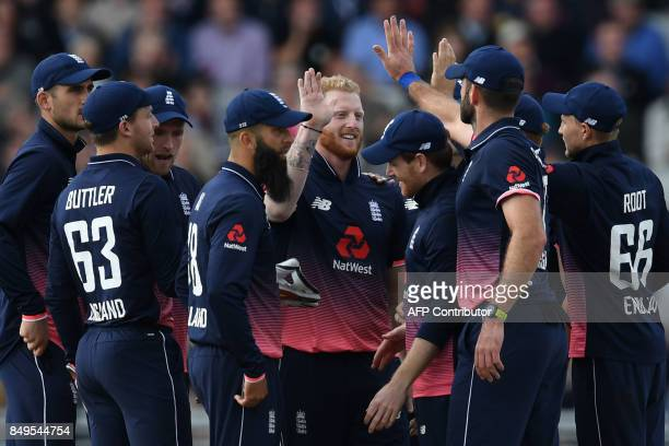 England's Ben Stokes celebrates with teammates the wicket of West Indies' Marlon Samuels for 17 during the first OneDay International cricket match...