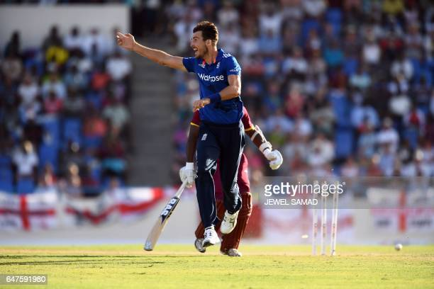 England's bowler Steven Finn celebrates after he kicks the ball to hit the wicket to run out West Indies cricketer Jason Mohammed during the One Day...