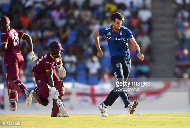 England's bowler Steven Finn kicks the ball to hit the wicket to run out West Indies cricketer Jason Mohammed during the One Day International match...