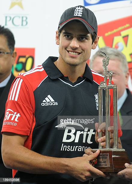 England's captain Alastair Cook gestures as he holds the trophy after victory in the fourth and final One Day International match between Pakistan...